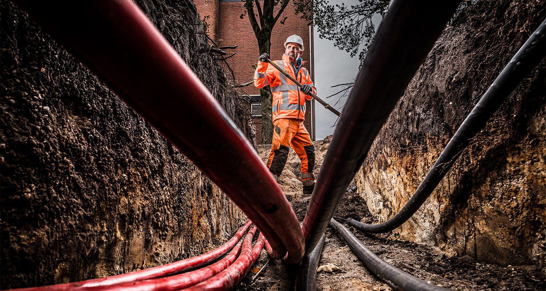 Een grondwerker aan het werk met leidingen en kabels.