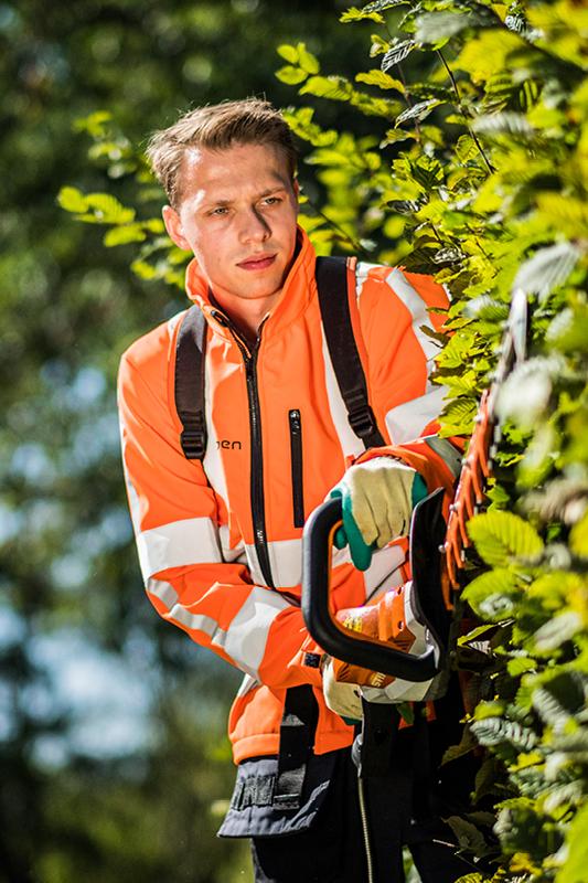 Medewerker groenvoorziening aan het werk met een heggenschaar.