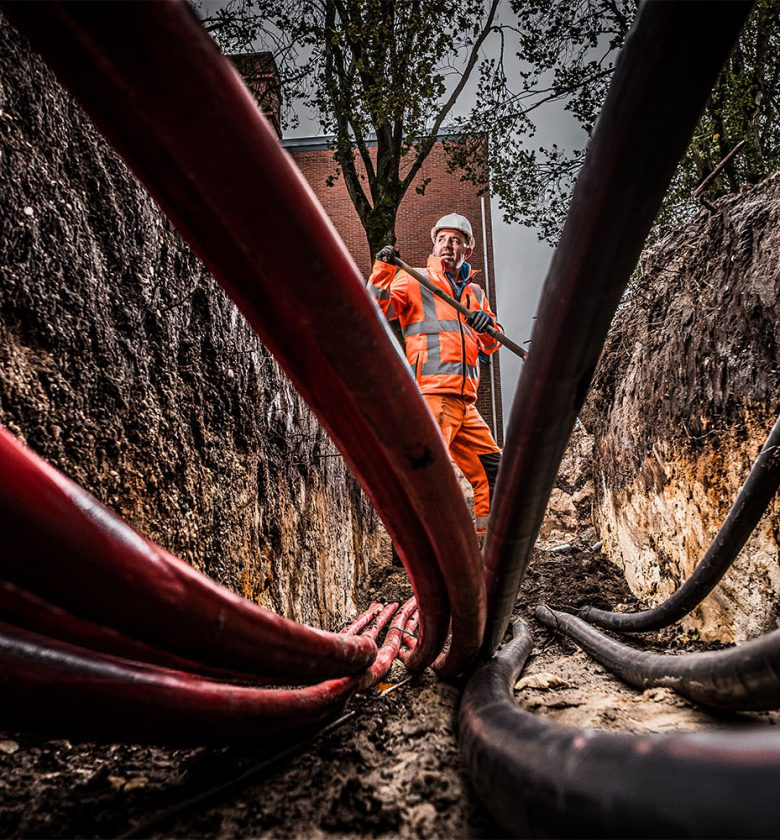 Grondwerker aan het werk tussen kabels en leidingen.