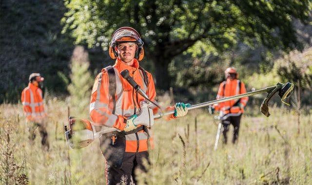 Een meewerkend voorman met medewerkers groenvoorziening aan het werk.
