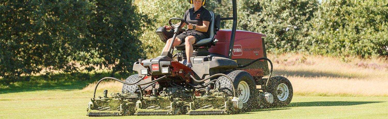 Greenkeeper op de maaimachine bezig op de golfbaan.