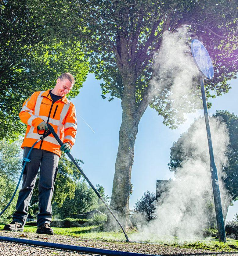 Medeweker groenvoorziening aan het werk met de onkruidverdelger.
