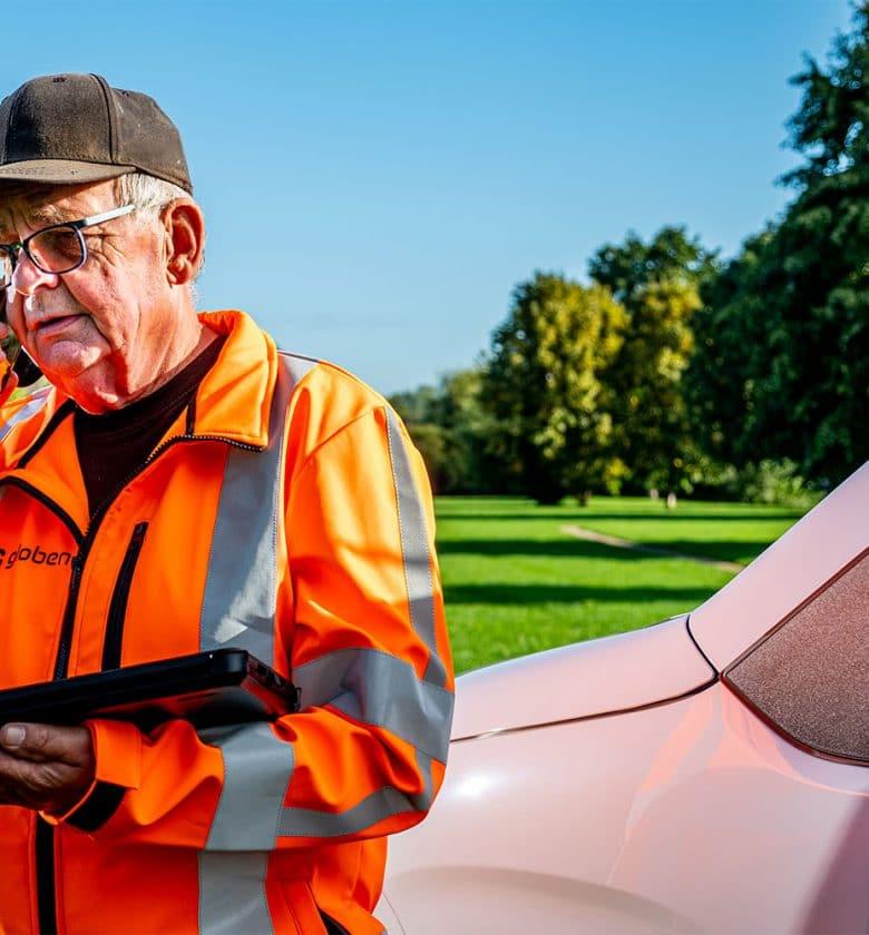 Medewerker Jan aan het telefoneren, terwijl hij werkt in de groenvoorziening