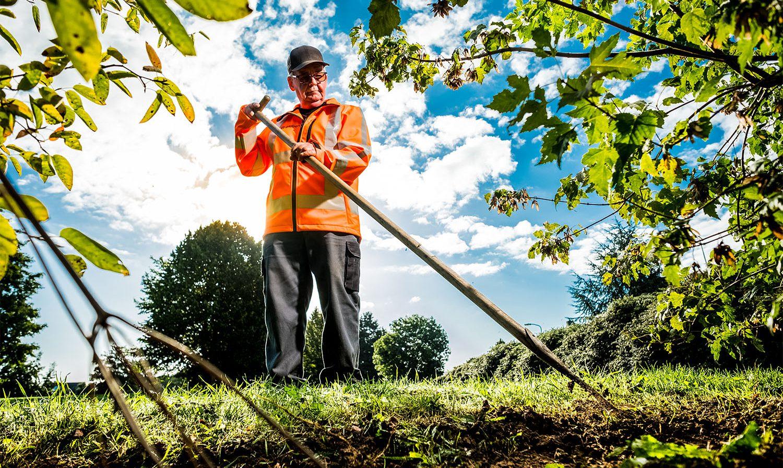 medewerker groenvoorziening aan het werk met een schoffel