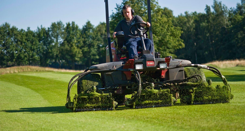 Greenkeeper aan het grasmaaien